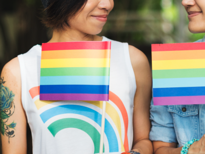 two women holding rainbow flags looking at each other